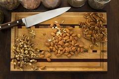 Υγιή καρύδια στον τέμνοντα πίνακα κουζινών, με το μαχαίρι Στοκ Εικόνες