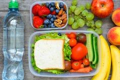 Υγιή καλαθάκια με φαγητό με το σάντουιτς και τα φρέσκα λαχανικά, το μπουκάλι νερό, τα καρύδια και τα φρούτα Στοκ εικόνα με δικαίωμα ελεύθερης χρήσης