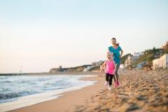 Υγιή μητέρα και κοριτσάκι που τρέχουν στην παραλία Στοκ φωτογραφία με δικαίωμα ελεύθερης χρήσης