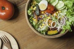 Υγιή πιάτα κύπελλων σαλάτας ξύλινα, ξύλινα και μαχαιροπήρουνα στο ξύλινο πάτωμα Στοκ εικόνες με δικαίωμα ελεύθερης χρήσης