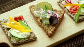 Υγιή σάντουιτς με τα φρέσκα λαχανικά Φρυγανιές προγευμάτων στον ξύλινο τέμνοντα πίνακα φιλμ μικρού μήκους