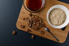 Υγιή συστατικά προγευμάτων: μέλι, ξύλα καρυδιάς, oatmeal στοκ φωτογραφία