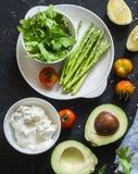 Υγιή συστατικά τροφίμων - αβοκάντο, σπαράγγι, ντομάτες, τυρί προβάτων, arugula στο σκοτεινό υπόβαθρο, τοπ άποψη Υγιής καθαρή κατα Στοκ Εικόνα