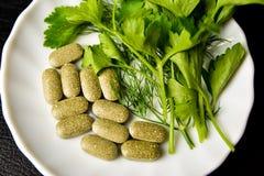 Υγιή τρόφιμα, εναλλακτικά τρόφιμα, μαϊντανός στα φύλλα και τις ταμπλέτες σε ένα άσπρο πιάτο στοκ φωτογραφία με δικαίωμα ελεύθερης χρήσης
