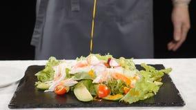 Υγιή τρόφιμα και χορτοφάγος έννοια Χύνοντας σάλτσα αρχιμαγείρων στο μαρούλι με τα λαχανικά που τοποθετούνται στο μαύρο πιάτο πετρ φιλμ μικρού μήκους