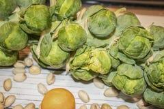 Υγιή τρόφιμα - κινηματογράφηση σε πρώτο πλάνο μέρους ενός μίσχου νεαρών βλαστών των Βρυξελλών που βάζει σε μια άσπρη σανίδα με έν στοκ φωτογραφία με δικαίωμα ελεύθερης χρήσης