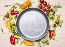 Υγιή τρόφιμα, μαγείρεμα και χορτοφάγα διάφορα λαχανικά έννοιας που σχεδιάζονται γύρω από το τηγάνι μετάλλων, πλαίσιο, διάστημα γι Στοκ Εικόνες