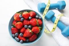 Υγιή φράουλες και βακκίνια σε ένα κύπελλο με τα βάρη και το μέτρο ταινιών Στοκ φωτογραφία με δικαίωμα ελεύθερης χρήσης