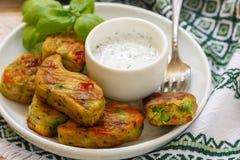 Υγιή χορτοφάγα patties πατατών με τα καρότα, το μπρόκολο, το πιπέρι κουδουνιών, τα πράσινα μπιζέλια και τα κρεμμύδια με την ξινή  Στοκ φωτογραφία με δικαίωμα ελεύθερης χρήσης