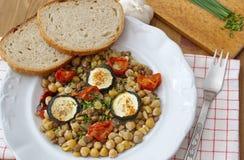 Υγιή vegan τρόφιμα - chickpeas, τα μπιζέλια και οι φακές εξυπηρέτησαν με τις ντομάτες, τα κολοκύθια, τα φρέσκα κρεμμύδια και το ψ Στοκ Φωτογραφία