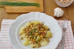 Υγιή vegan τρόφιμα - chickpeas, τα μπιζέλια και οι φακές εξυπηρέτησαν με τις πατάτες και το φρέσκο κρεμμύδι Στοκ φωτογραφία με δικαίωμα ελεύθερης χρήσης