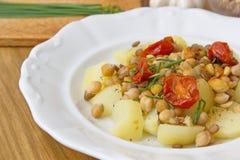 Υγιή vegan τρόφιμα - chickpeas, τα μπιζέλια και οι φακές εξυπηρέτησαν με τις ντομάτες και το φρέσκο κρεμμύδι Στοκ Εικόνες