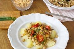 Υγιή vegan τρόφιμα - chickpeas, τα μπιζέλια και οι φακές εξυπηρέτησαν με τις ντομάτες και το φρέσκο κρεμμύδι Στοκ φωτογραφίες με δικαίωμα ελεύθερης χρήσης