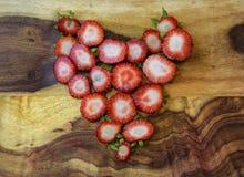 Υγιείς ακατέργαστες φράουλες καρδιών στον τέμνοντα πίνακα Στοκ Φωτογραφία