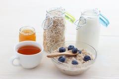 Υγιείς νιφάδες βρωμών κατανάλωσης των βακκινίων και του τσαγιού με το μέλι Στοκ Φωτογραφίες