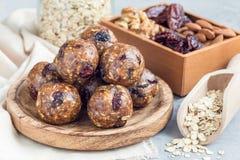 Υγιείς σπιτικές ενεργειακές σφαίρες με τα τα βακκίνια, τα καρύδια, τις ημερομηνίες και τις κυλημένες βρώμες στο ξύλινο πιάτο, ορι Στοκ Εικόνες