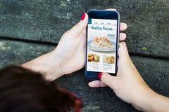 υγιείς συνταγές τοπ άποψης smartphone γυναικών επιτραπέζιου στοκ φωτογραφία με δικαίωμα ελεύθερης χρήσης