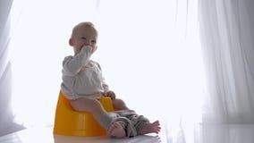 Υγιεινή μωρών, συνεδρίαση νηπίων γέλιου συμπαθητική στο chamberpot στο φωτεινό δωμάτιο φιλμ μικρού μήκους