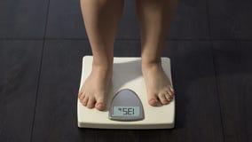 Υγιεινό να κάνει δίαιτα, κορίτσι που στέκεται στις κλίμακες λουτρών για να ελέγξει το βάρος, κανονικός δείκτης στοκ φωτογραφία με δικαίωμα ελεύθερης χρήσης