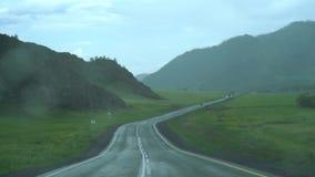 Υγρός δρόμος στα βουνά, μπλε ουρανός με τα σύννεφα στην απόσταση ψήκτρες έντονου φωτός και ανεμοφρακτών απόθεμα βίντεο