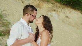 Υγρός μετά από ένα αγαπώντας ζεύγος βροχής που φιλά στην παραλία απόθεμα βίντεο
