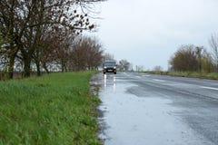 Υγρός προαστιακός δρόμος με το αυτοκίνητο στοκ εικόνες με δικαίωμα ελεύθερης χρήσης