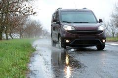 Υγρός προαστιακός δρόμος με το αυτοκίνητο στοκ φωτογραφία