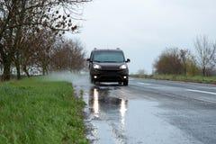 Υγρός προαστιακός δρόμος με το αυτοκίνητο στοκ φωτογραφίες