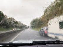 Υγρό αλεξήνεμο από τη βροχή που προσπερνά το αυτοκίνητο που ρυμουλκεί ένα τροχόσπιτο Στοκ εικόνα με δικαίωμα ελεύθερης χρήσης
