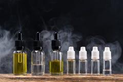 Υγρό με τα νόστιμα αρώματα στα μπουκάλια για ένα ηλεκτρονικό τσιγάρο, σε ένα κλίμα του ατμού Στοκ εικόνες με δικαίωμα ελεύθερης χρήσης