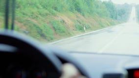 Υγρό οδόστρωμα στη βροχερή ημέρα, οδήγηση αυτοκινήτων στον τραχύ δρόμο στη βροχή απόθεμα βίντεο