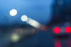 Υγρό παράθυρο με το υπόβαθρο της πόλης νύχτας Στοκ Εικόνες