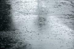 Υγρό πεζοδρόμιο με τις σταγόνες βροχής στις λακκούβες κατά τη διάρκεια της δυνατής βροχής Στοκ Εικόνες