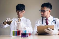 Υγρό substrance δοκιμής δύο ατόμων επιστημόνων στο εργαστήριο Στοκ φωτογραφία με δικαίωμα ελεύθερης χρήσης