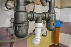 Υδάτινο σύστημα με τις στρόφιγγες, το σιφώνιο αποξηράνσεων και το φίλτρο νερού στοκ φωτογραφία