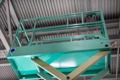 Υδραυλική πλατφόρμα ανελκυστήρων ψαλιδιού Η πλατφόρμα του ανελκυστήρα αυξάνεται κάτω από τη στέγη του κτηρίου στοκ εικόνες