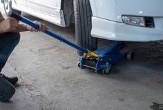 Υδραυλικός γρύλος αυτοκινήτων για να ανυψώσει το αυτοκίνητο για τον έλεγχο η ρόδα στοκ εικόνες με δικαίωμα ελεύθερης χρήσης