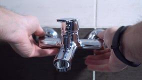 Υδραυλικός που εγκαθιστά μια βρύση αναμικτών σε ένα λουτρό, κάθεται στην κινηματογράφηση σε πρώτο πλάνο μπανιέρων απόθεμα βίντεο