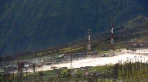 Υδρονέφωση που ρέει πέρα από το χωριό Cemoro Lawang το πρωί που βρίσκεται βόρειο-ανατολικά της ΑΜ Bromo, Ινδονησία στοκ εικόνα