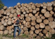 Υλοτόμος με το αλυσιδοπρίονο και τσεκούρι στο δάσος Στοκ φωτογραφία με δικαίωμα ελεύθερης χρήσης