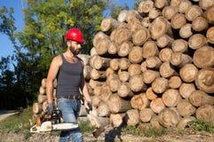Υλοτόμος με το αλυσιδοπρίονο και τσεκούρι στο δάσος Στοκ εικόνες με δικαίωμα ελεύθερης χρήσης