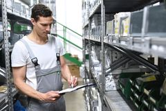 Υπάλληλοι ενός καταστήματος επισκευής αυτοκινήτων σε μια αποθήκη εμπορευμάτων για τα ανταλλακτικά - Στοκ εικόνες με δικαίωμα ελεύθερης χρήσης