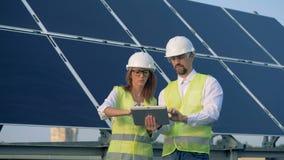 Υπάλληλοι κατασκευής στο στάδιο της συζήτησης και του προγραμματισμού στεμένος εκτός από ένα ηλιακό πλαίσιο απόθεμα βίντεο