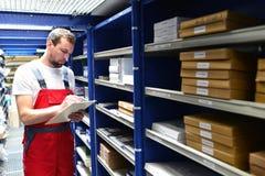 Υπάλληλοι καταστημάτων επισκευής αυτοκινήτων στην αποθήκη εμπορευμάτων για τα ανταλλακτικά για το ρ Στοκ Εικόνα