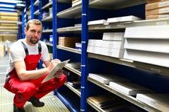 Υπάλληλοι καταστημάτων επισκευής αυτοκινήτων στην αποθήκη εμπορευμάτων για τα ανταλλακτικά για το ρ Στοκ Φωτογραφία
