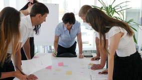 Υπάλληλοι που συζητούν ο ένας με τον άλλον της επιχειρησιακής διαπραγμάτευσης κοντά στον πίνακα στην εργασία φιλμ μικρού μήκους