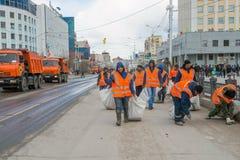 Υπάλληλοι που συλλέγουν τα απορρίματα στο κέντρο πόλεων μια δυσάρεστη ημέρα στοκ εικόνα