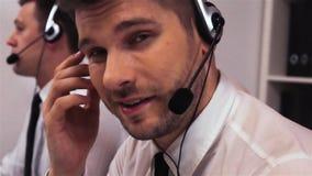 Υπάλληλος δύο με τις κάσκες που μιλούν στο κέντρο φωνητικής κλίσης απόθεμα βίντεο