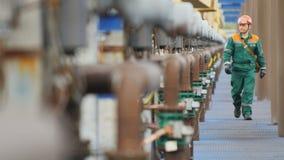 Υπάλληλος με τους περιπάτους τσαντών από τους αγωγούς υγραερίου στις εγκαταστάσεις φιλμ μικρού μήκους