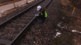 Υπάλληλος σιδηροδρόμων γυναικών που γράφει κοντά στο σιδηρόδρομο απόθεμα βίντεο